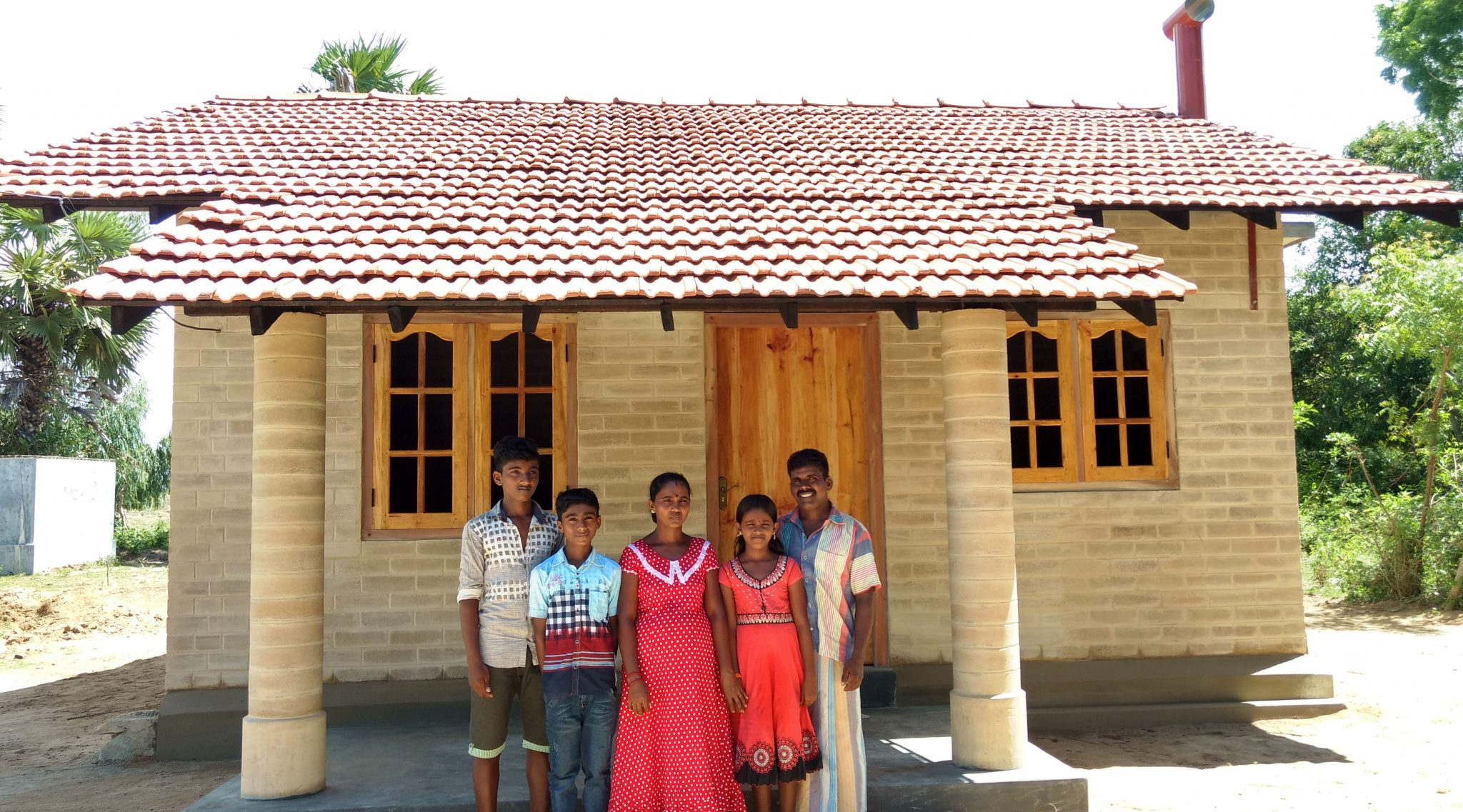 Thillainathan (far right) and Ushathevi (center) with their children (from left) Dinesh, Shanmugasivam and Aishwarya in front of their Habitat house after it was completed in August 2017. Photo: Habitat for Humanity/Jim Kendall.